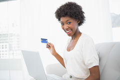 Smiling gorgeous brunette using her credit card to buy online stock images