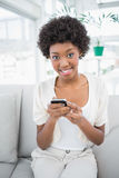 Smiling gorgeous brunette using her smartphone Stock Image