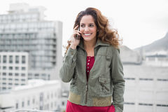 Smiling gorgeous brunette in winter fashion phoning Stock Image