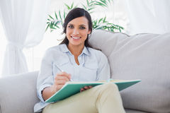 Smiling gorgeous brunette writing while sitting on the sofa Royalty Free Stock Photos
