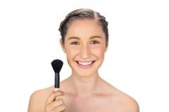Smiling gorgeous model holding blusher brush Stock Photography