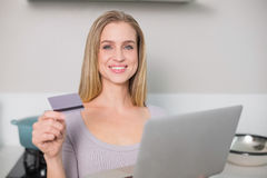 Smiling gorgeous model holding laptop and credit card Royalty Free Stock Images