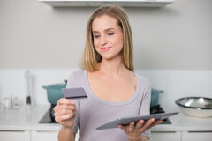Smiling gorgeous model holding tablet and credit card Royalty Free Stock Photography