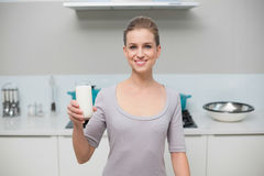 Smiling gorgeous model looking at camera holding glass of milk Royalty Free Stock Photography