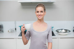 Smiling gorgeous model looking at camera holding mug Stock Photography