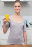 Smiling gorgeous model looking at camera holding orange juice Stock Photography