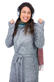 Smiling gorgeous model with winter clothes dancing while listening to music Royalty Free Stock Photo