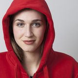 Smiling gorgeous 20s female student wearing red sportwear clothes. Natural smile - closeup portrait of beautiful smiling 20s woman wearing red hood sweater for Stock Photo