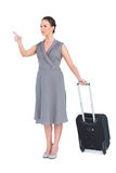 Smiling gorgeous woman carrying her suitcase pointing finger Stock Photos
