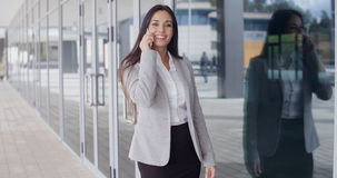 Smiling gorgeous woman on phone outside office Royalty Free Stock Image