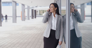 Smiling gorgeous woman on phone outside office Royalty Free Stock Photo