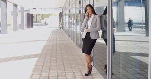 Smiling gorgeous woman on phone outside office Stock Photography