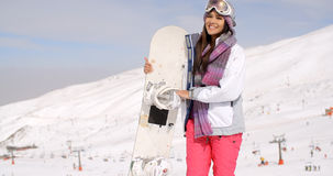 Smiling gorgeous woman posing with her snowboard Stock Images