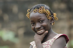 Smiling gorgoeus little black African girl smiling outdoors. Young african girl with traditional accessories in hair looking at camera Stock Images