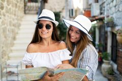 Smiling gorup of friends with map. Tourism, travel, leisure, holidays and friendship concept. Tourism, travel, leisure, holidays and friendship concept - smiling stock images