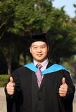 Smiling graduate. Happy university graduate with thumbs up Stock Photo