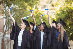 Smiling graduate school kids standing with degree scroll in campus Stock Images