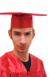Smiling graduate student in red cap and gown Stock Image