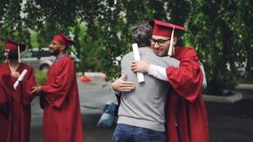 Smiling graduating student is shaking his father`s hand and hugging him, young man in glasses is wearing hat and gown. And holding diploma. Education, family stock footage