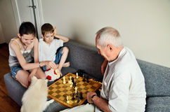 Smiling grandchildren with grandpa playing chess and looking at Royalty Free Stock Photo