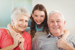 Smiling granddaughter embracing her grandparents in living room Stock Photos