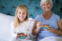 Smiling granddaughter and grandmother having breakfast on bed. Portrait of smiling granddaughter and grandmother having breakfast on bed Stock Photo