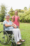 Smiling granddaughter with grandmother in her wheelchair Royalty Free Stock Photos