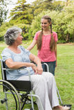 Smiling granddaughter with grandmother in her wheelchair Royalty Free Stock Image