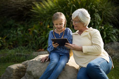 Smiling granddaughter and grandmother using digital tablet in garden. On a sunny day Stock Image