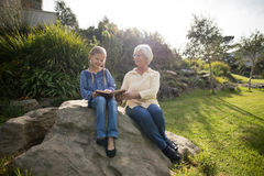 Smiling granddaughter and grandmother using digital tablet in garden. On a sunny day Royalty Free Stock Photos
