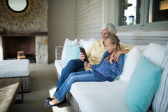 Smiling granddaughter and grandmother using digital tablet on sofa Royalty Free Stock Photography