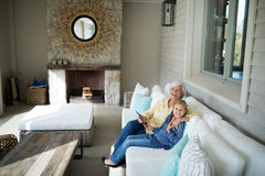 Smiling granddaughter and grandmother using digital tablet on sofa Royalty Free Stock Images