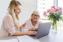 Smiling granddaughter and grandmother using laptop computer. At home Royalty Free Stock Photos