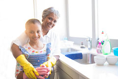 Smiling granddaughter and grandmother wearing kitchen gloves in kitchen. Portrait of smiling granddaughter and grandmother wearing kitchen gloves in kitchen at Royalty Free Stock Photo