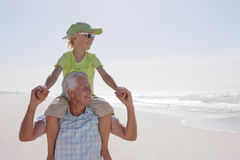 Smiling grandfather carrying grandson on shoulders on sunny beach Stock Photos