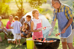 Smiling grandfather giving granddaughter grilling meat Stock Images