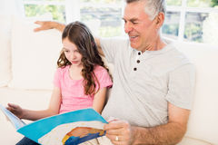 Smiling grandfather and granddaughter reading book Stock Photos