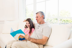 Smiling grandfather and granddaughter reading book Royalty Free Stock Photo