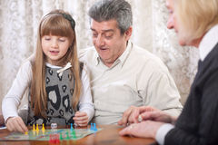 Smiling grandfather, grandmother and granddaughter playing board Royalty Free Stock Photo