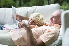 Smiling grandfather and grandson laying on outdoor sofa with digital tablet Royalty Free Stock Image