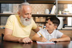 Smiling grandfather helping his grandson with math assignment. Caring grandfather. Joyful senior men sitting next to his beloved little grandson and helping him Stock Photo