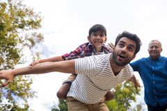 Smiling grandfather looking at man giving piggy backing to son Royalty Free Stock Images