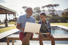 Smiling grandfather showing laptop to grandson near poolside. On a sunny day stock photography