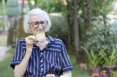 Smiling grandma having cup of coffee outdoors Stock Photos
