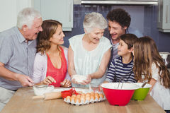 Smiling grandmother cooking food with family Stock Images
