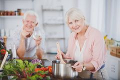 Smiling grandmother cooking tomato soup. Smiling grandmother cooking healthy tomato soup for her happy husband Royalty Free Stock Photography