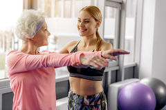 Smiling grandmother dealing with coach in gym Royalty Free Stock Photos