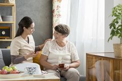 Smiling grandmother drinking tea. Friendly women talking to a smiling grandmother drinking tea during a visit Stock Image