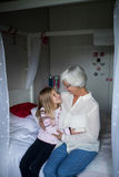 Smiling grandmother and granddaughter embracing each other on bed. In bedroom Royalty Free Stock Photography