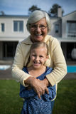 Smiling grandmother and granddaughter embracing each other in garden. Portrait of smiling grandmother and granddaughter embracing each other in garden on a sunny Stock Images